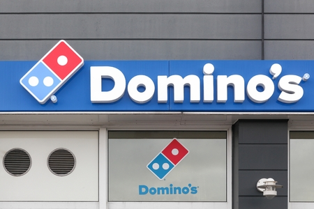 Viby, Denmark - March 24, 2019: Domino's pizza logo on a wall of a restaurant. Domino's pizza is an American pizza restaurant chain founded in 1960