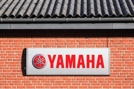 Skanderborg, Denmark - July 16, 2019: Yamaha logo on a wall. Yamaha is a Japanese multinational corporation with a wide range of products like musical instruments, electronics and motorcycles Editorial