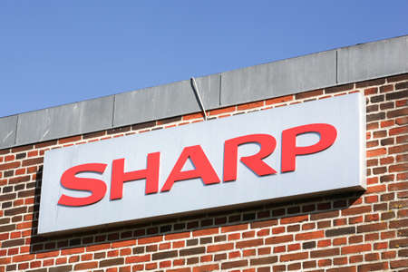 Ega, Denmark - May 11, 2019: Sharp logo on a facade. Sharp is a Japanese multinational corporation that designs and manufactures electronic products Redakční