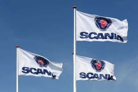 Vejle, Denmark - September 10, 2016: Scania flags waving in the sky. Scania is a major swedish automotive industry manufacturer of commercial vehicles specifically heavy trucks and buse