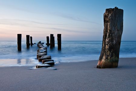 paisagem: Old groyne on the shore of the Baltic Sea.