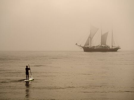 A surf kayaker and a sailing ship on the Baltic Sea  photo