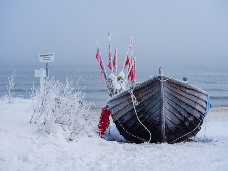 A fishing boat on shore of the Baltic Sea in winter