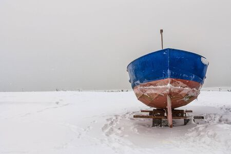 A fishing boat on shore of the Baltic Sea in winter  photo