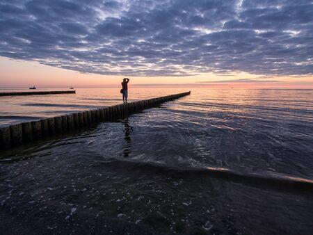 groyne: Fotographer on a groyne on shore of the Baltic Sea.