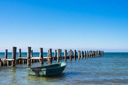 groyne: Groyne and fishing boat on the Baltic Sea coast in Zingst (Germany). Stock Photo