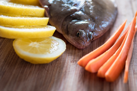 limon: A fresh flunder with lemon slices and carrots slices. Stock Photo