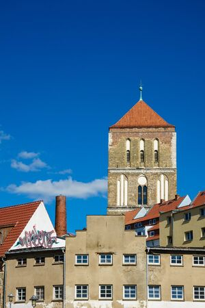 Buildings with church in Rostock (Germany) with blue sky.