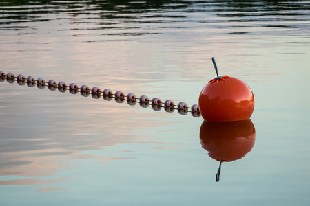 Buoy on a lake with reflection in the evening.