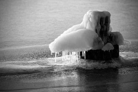 icicled: Frozen bollard on a river in winter. Stock Photo