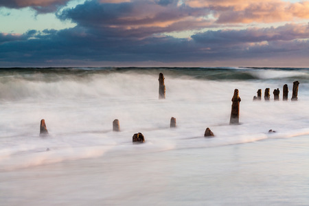 groynes: Groynes on shore of the Baltic Sea on a stormy day. Stock Photo