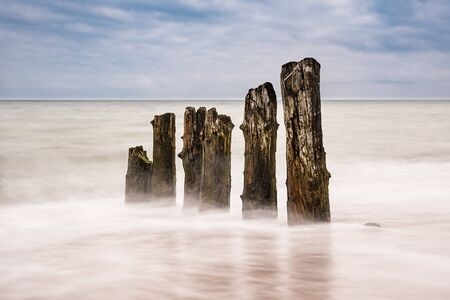 groyne: Groynes on shore of the Baltic Sea in the evening. Stock Photo