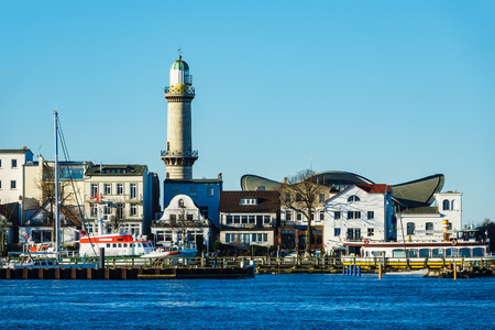 Buildings, lighthouse and blue sky in Warnemuende, Germany.
