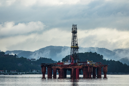View to the Lyngdalsfjord with drilling rig in Norway. Stock Photo