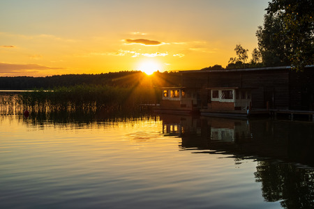 Landscape on a lake with trees and boatshouse. Standard-Bild - 112529397