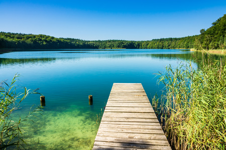 Landscape on a lake with trees and blue sky. Standard-Bild - 112529417