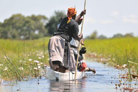 A woman is going by mokoro canoe through the okavango delta Stock Photo