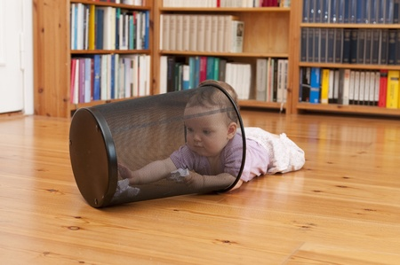 Toddler plays with wastebasket Stock Photo