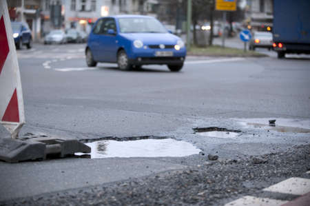 pothole: pot-hole in a street with many traffic
