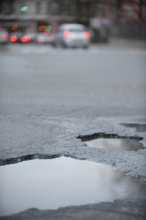 pot-hole in a street with many traffic