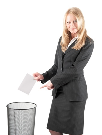 Middle aged woman casting a letter in the waste paper bin on isolated background