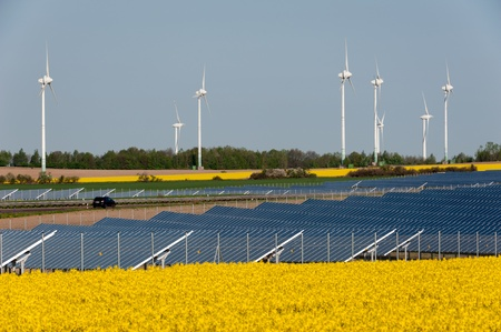 eco sensitive: Wind turbines and solar panels in a rapeseed field Stock Photo