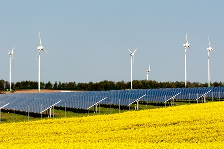 Wind turbines and solar panels in a rapeseed field Stock Photo