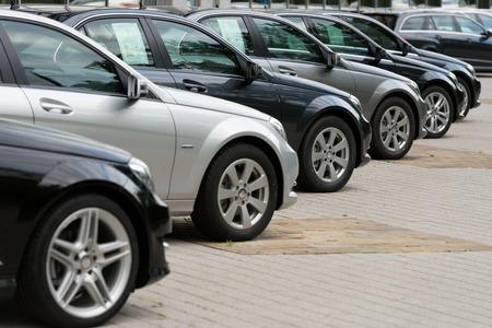 hilera: Coches a la venta en un lugar de estacionamiento Editorial