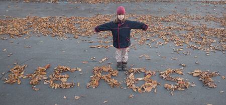 age 5: Girl of 5 years age with writing autumn