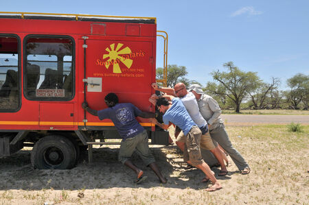 activ: Kalahari, Botswana - January 1, 2009: People push car from sand hole Editorial