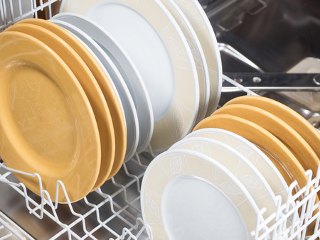 automatically: open dishwasher with different colored ans sized plates Stock Photo