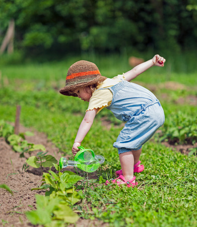 Kid with hat pouring water to vegetable