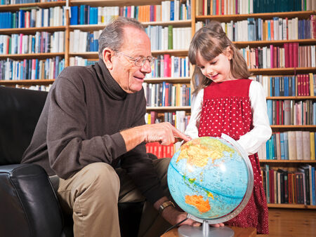 Grandfather and granddaughter looking at a globe photo