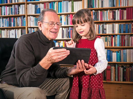 Senior and granddaughter looking at a tablet photo