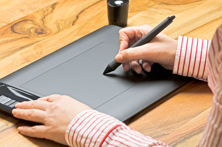 art processing: Hand with graphics tablet on a board