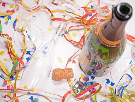 an open bottle of champagne with confetti