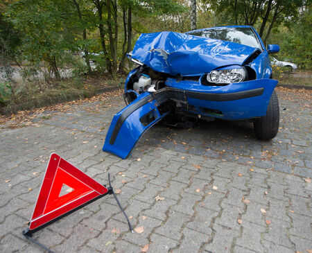 Damaged blue car with red warning triangle