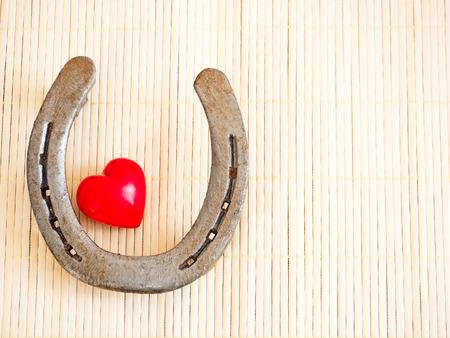 Horseshoe and heart on a background of bast fibers Stock Photo