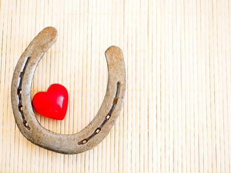bast: Horseshoe and heart on a background of bast fibers Stock Photo