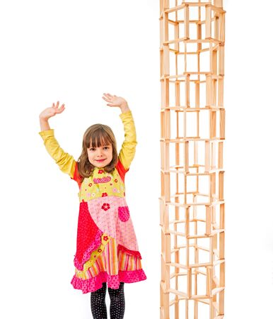 relational: Child standing next to a tower out of blocks