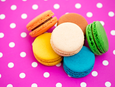 closeup of colorful macarons on pink background