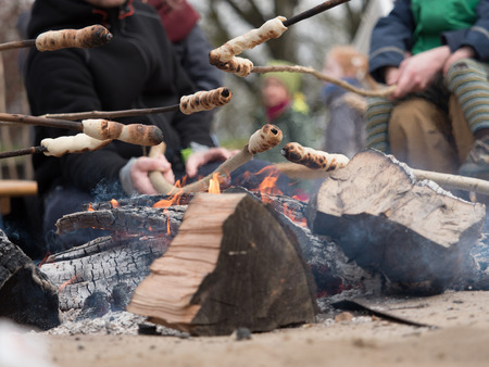 Family grilling bread on a stick over an open fire Stock Photo