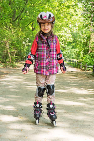elbow pads: Child drives Roller Skates in a park