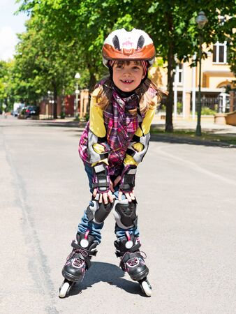 elbow pads: Child drives Roller Skates on the street Stock Photo