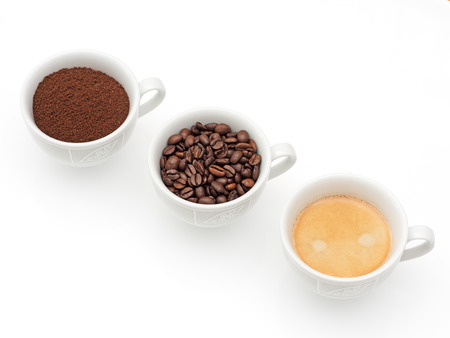 Three cups with coffee, coffee beans and ground coffee