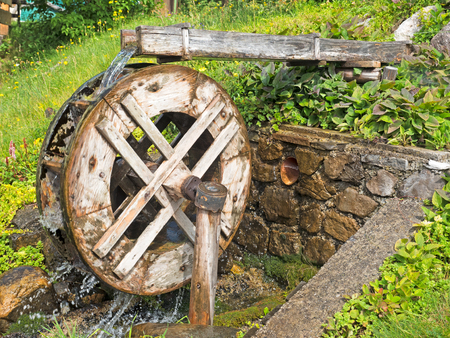 hydropower: rotating old Watermill by a little stream Stock Photo