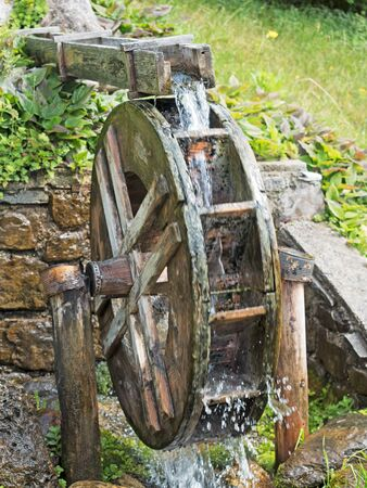 rotating old Watermill by a little stream Stock Photo