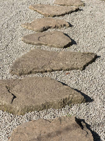 stepping on: Stepping stones on a gravel road in a park Stock Photo