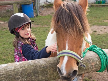 Child with helmet stroking pony on a farm
