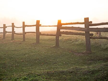 Paddock fence at sunrise on an autumn day